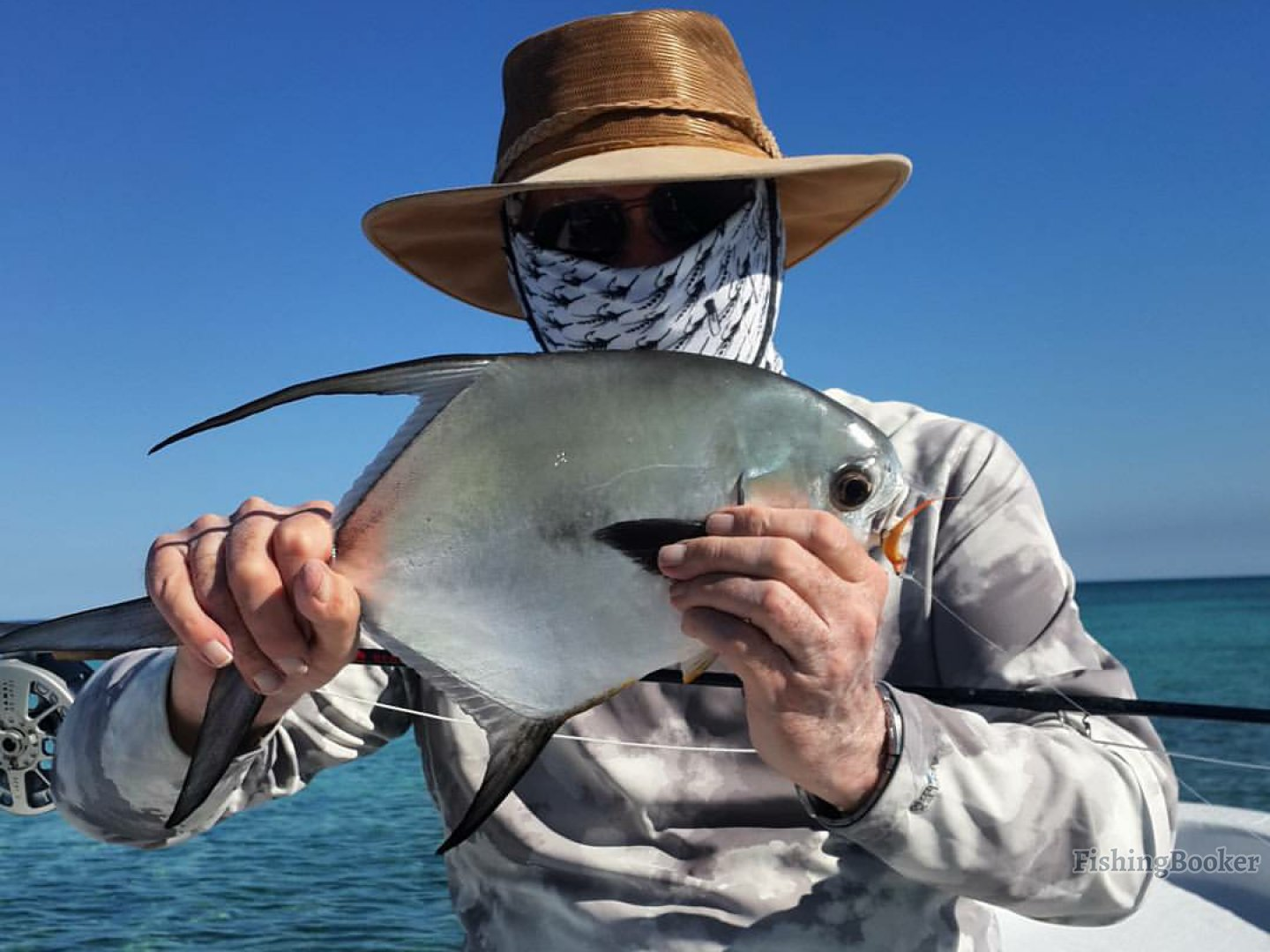 a angler holding a permit fish in Belize