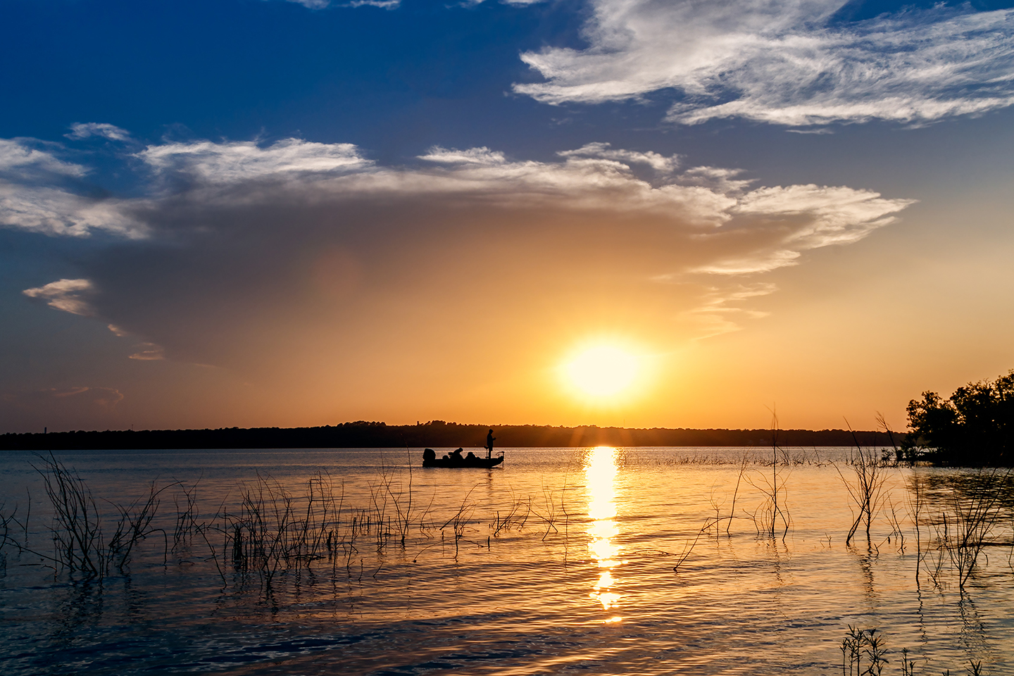 A small boat on a lake in Oklahoma at sunset, with a person fishing off the front of it