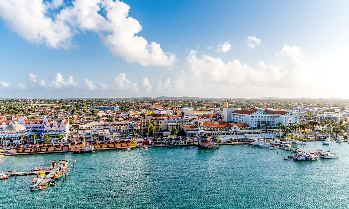 The waterfront in Oranjestad, Aruba, with brightly-colored buildings and green-blue sea.