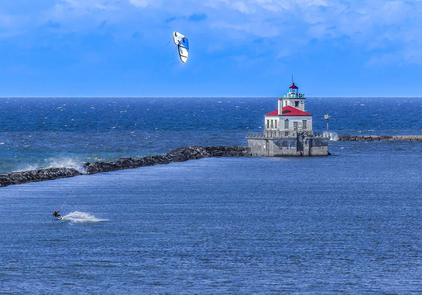 A kite-surfer on Lake Ontario with Oswego's lighthouse behind him.