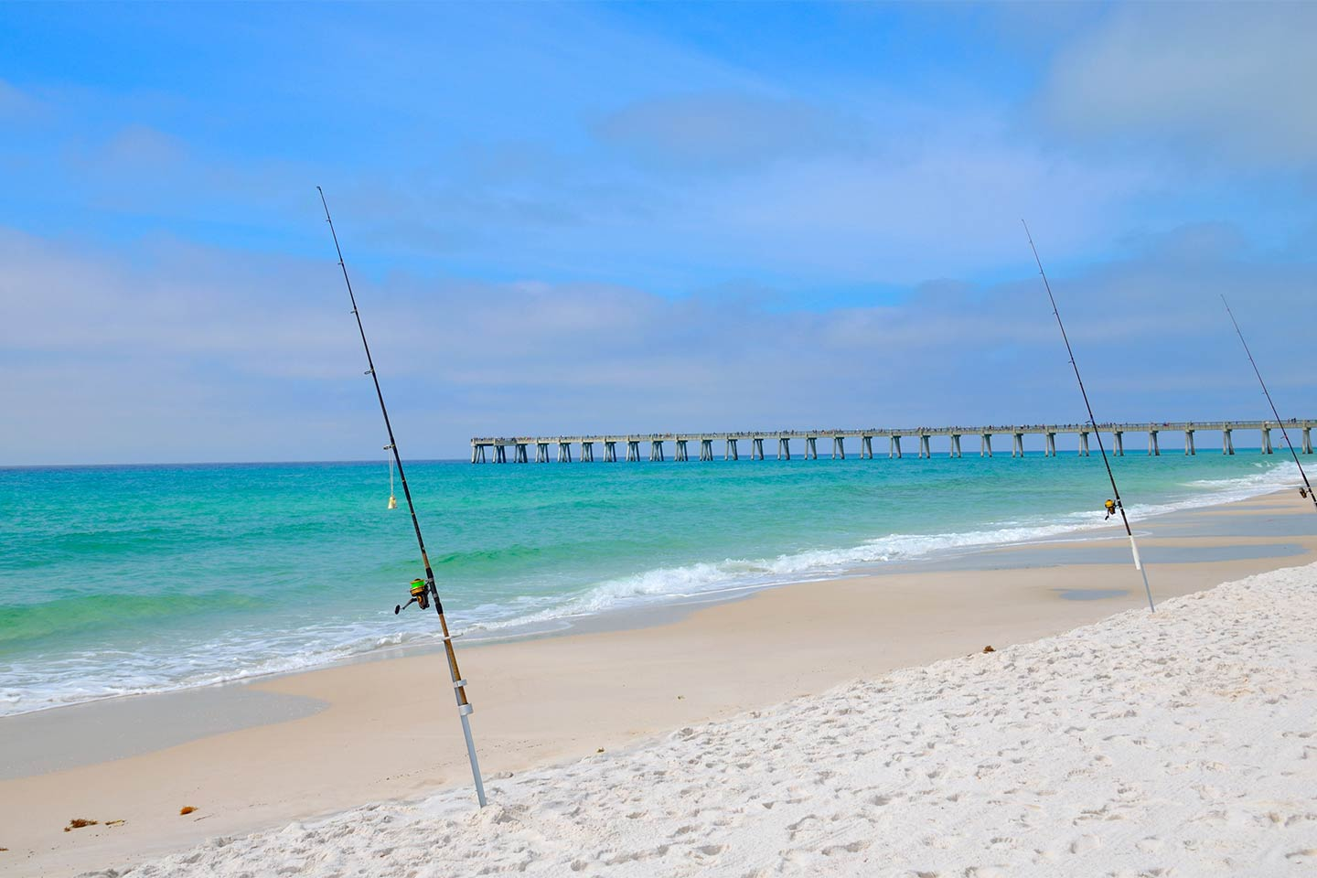 Three fishing rods perched in the sand with a Panama City Beach fishing pier in the background