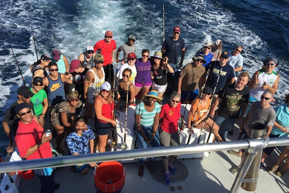A large group of anglers at the back of a party charter boat
