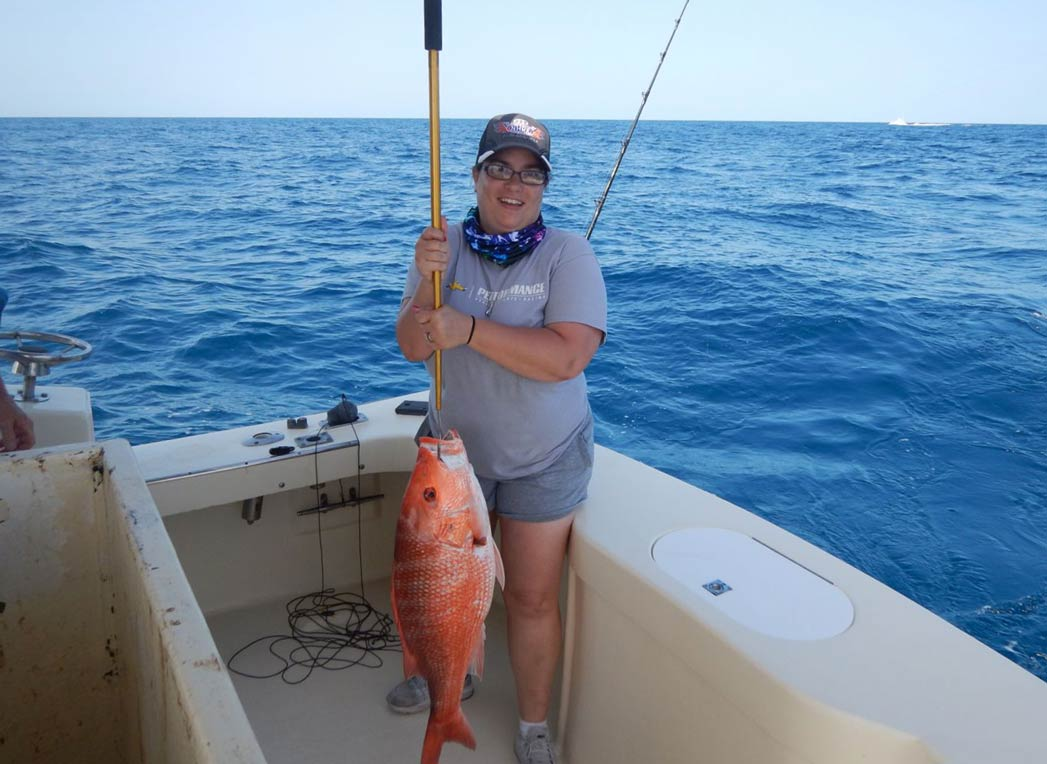 Image shows a woman holding a large Redfish on board Patriot Charters