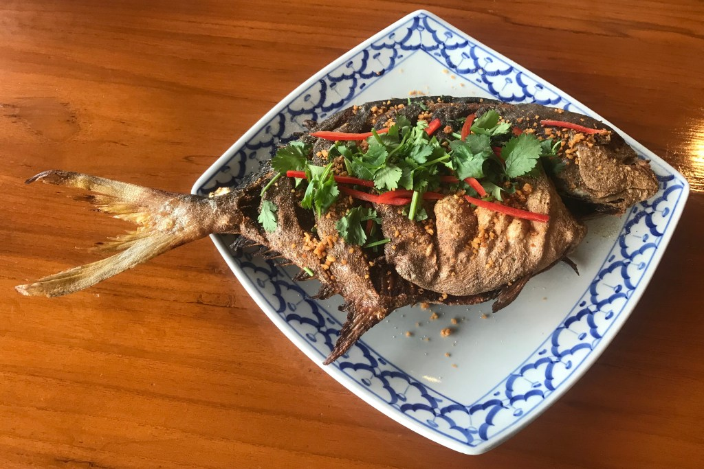 A whole fried Pompano fish on a plate, with cilantro and red chilli scattered on top