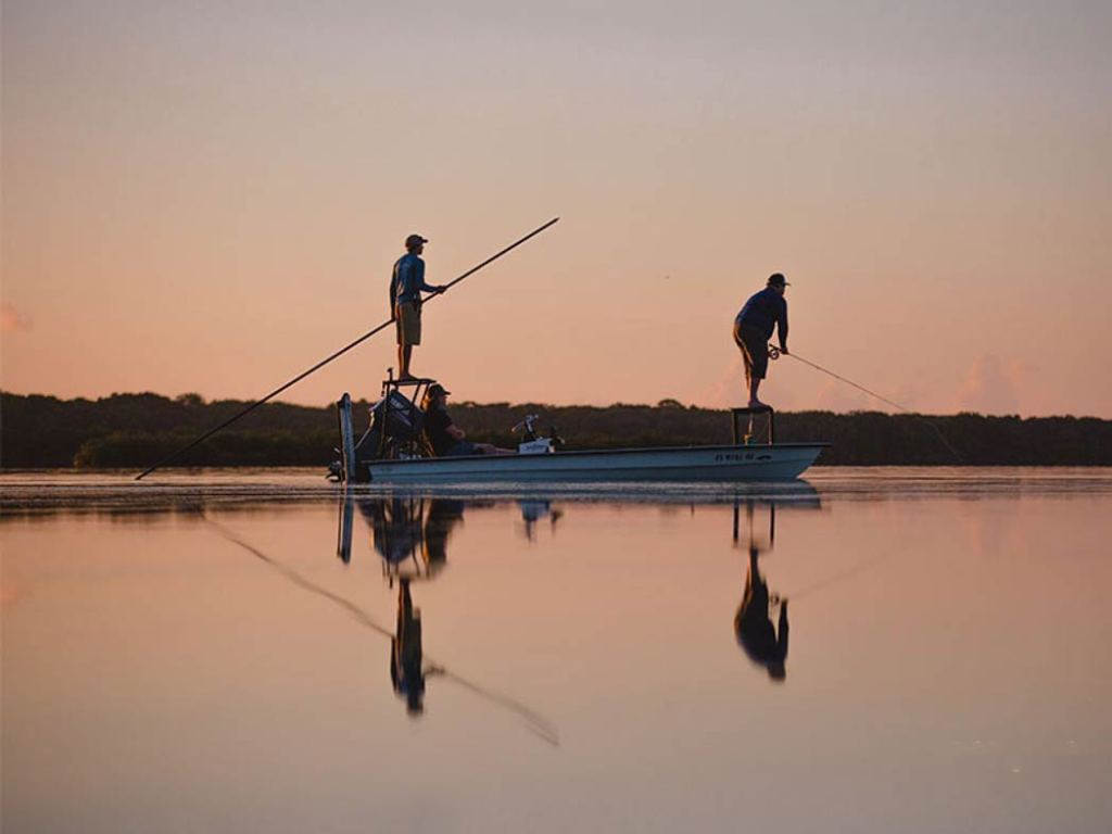 Two anglers pole across the flats of the Indian River at sunset