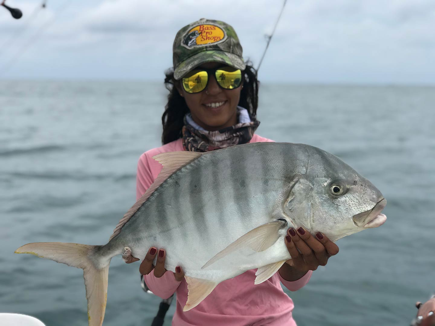 A female angler holds a Trevally  caught in Puerto Vallarta
