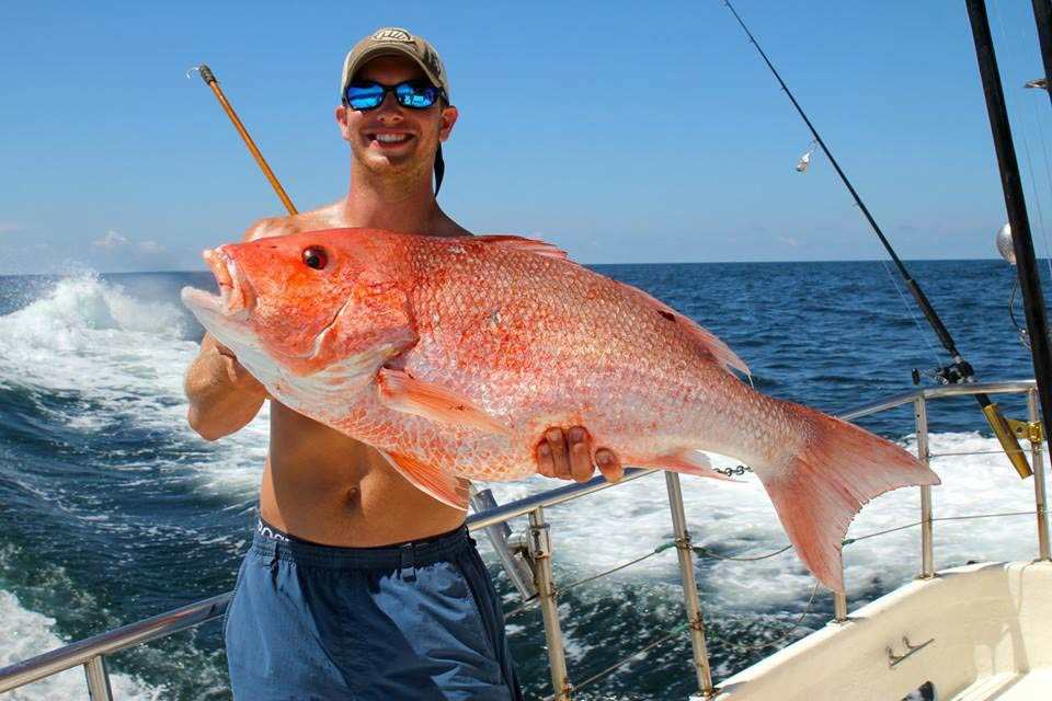 An angler holds a large Red Snapper with the waves crashing behind him in the Gulf of Mexico