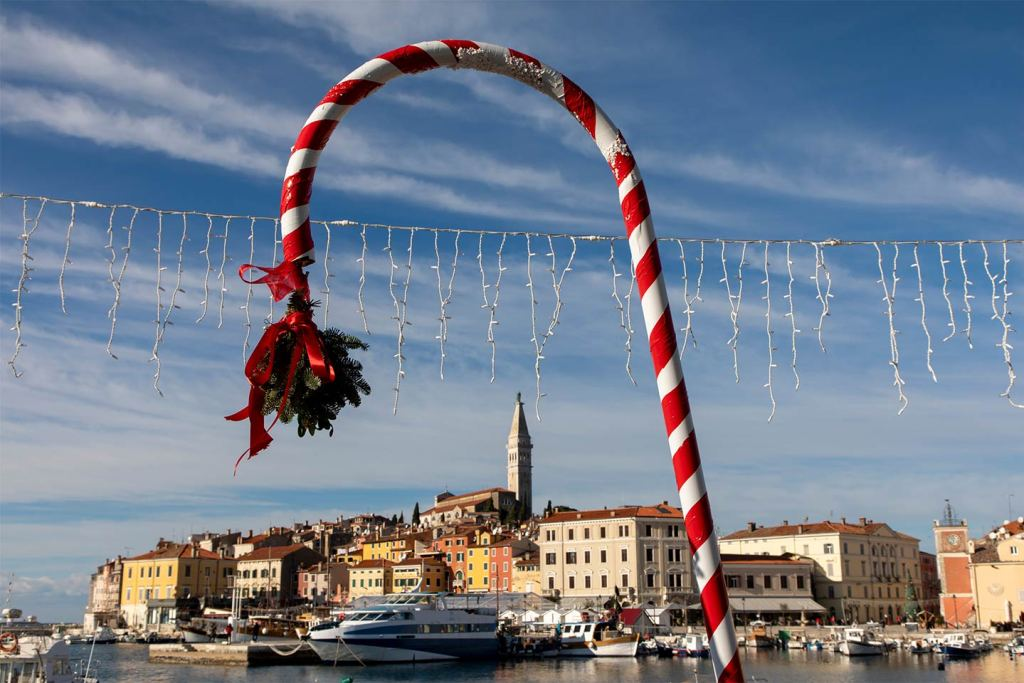 A candy cane Christmas decoration in the foreground hangs over the town of Rovinj and its church spire in the background