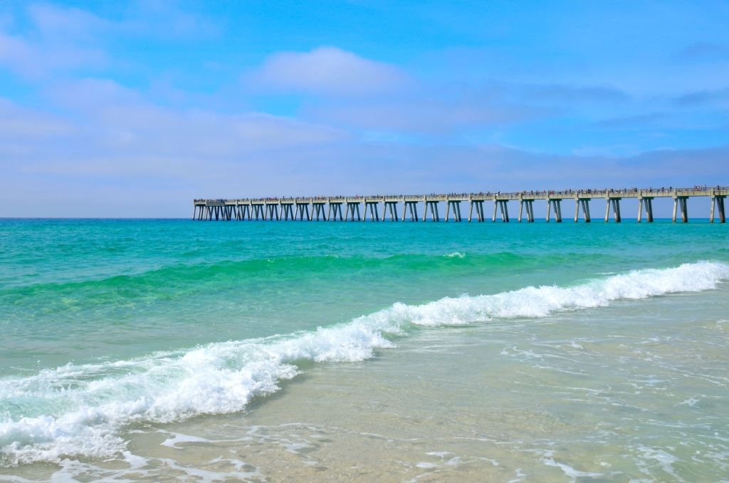 A long wooden pier in the sea, with clear water and white sand in the foreground