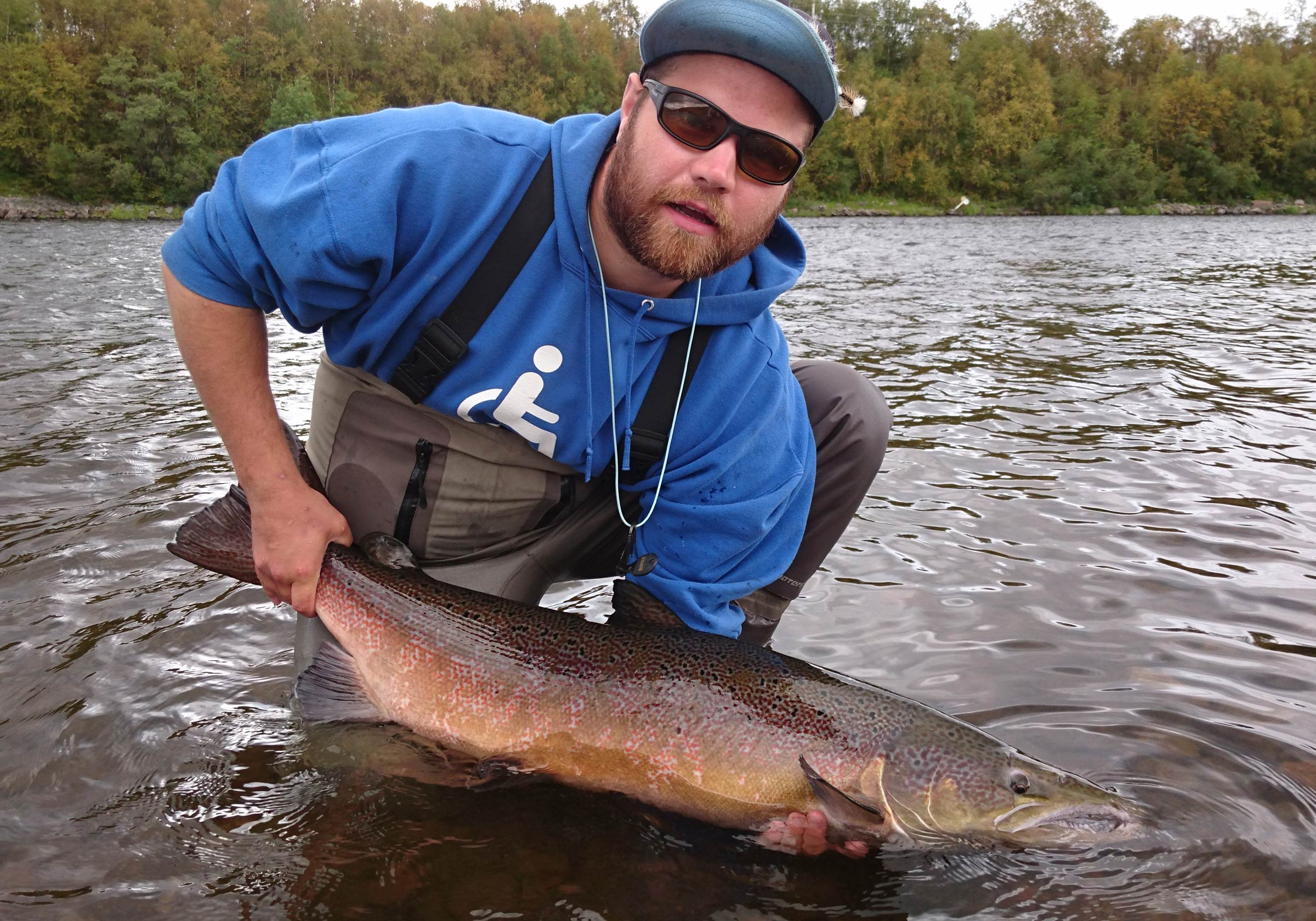 An angler with sunglasses and a cap squatting in running water, holding a nice-sized Salmon