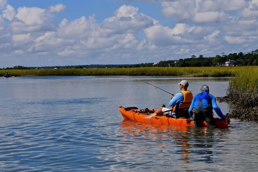 A kayak angler at a fishing therapy session being pushed out into calm water by a volunteer