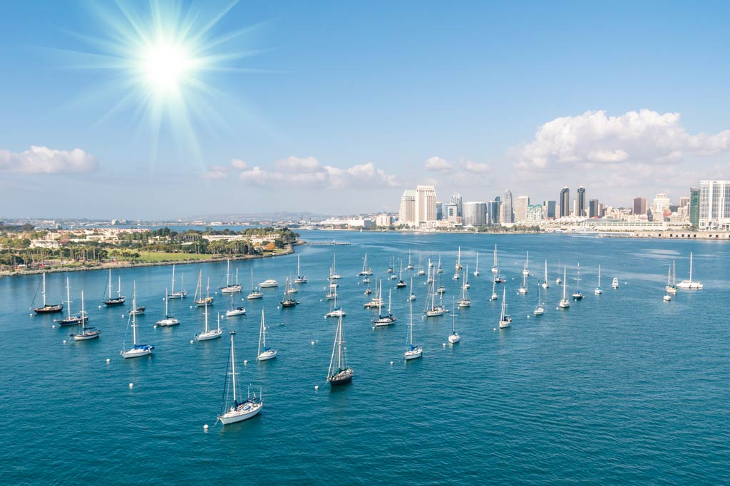 Sailboats pictured in the water alongside San Diego's water front and skyline