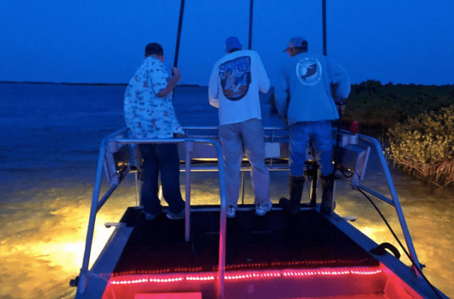 Three men gigging at night on a lighted boat