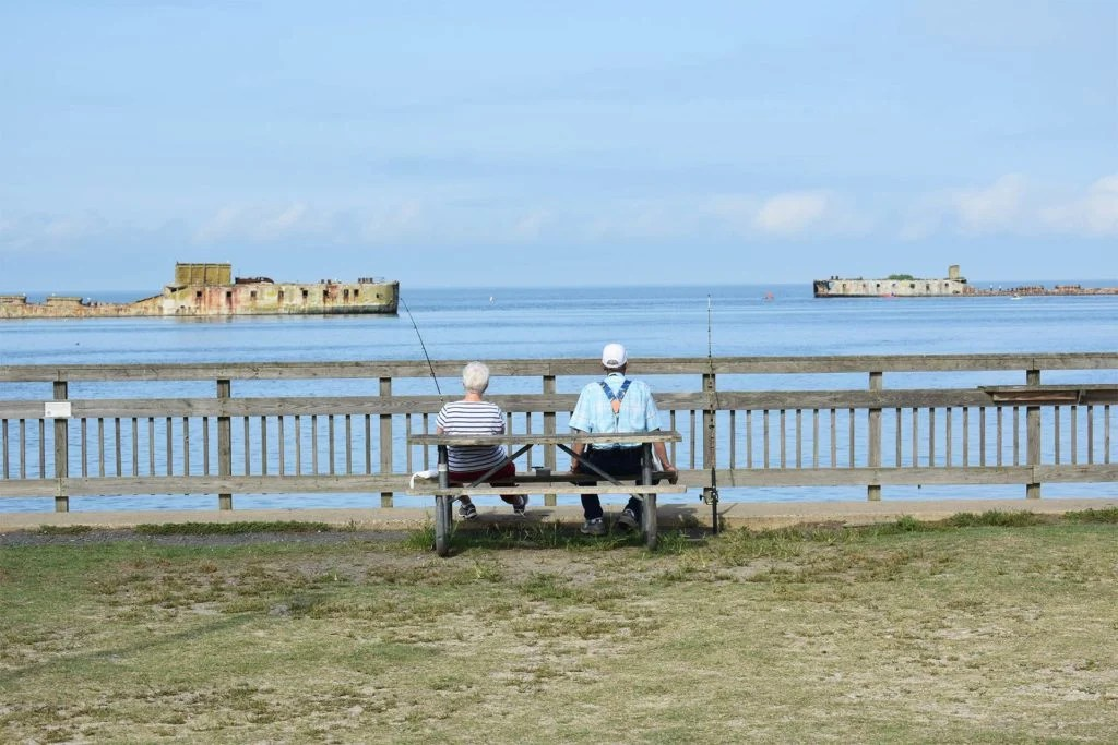 Two anglers sit on a bench fishing from shore in the Chesapeake Bay