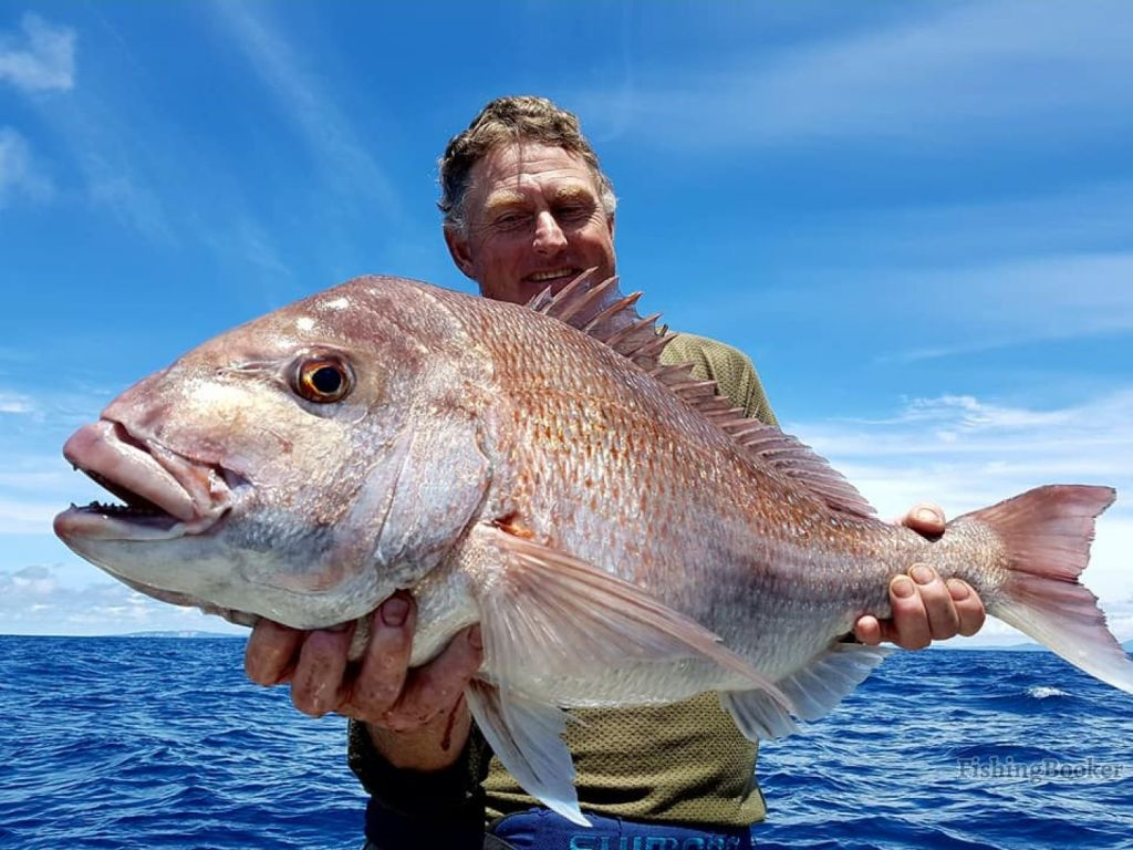 a smiling angler fishing for the first time is holding a fish