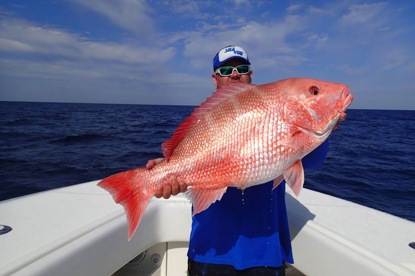 A man holding a big Red Snapper on a boat in Florida