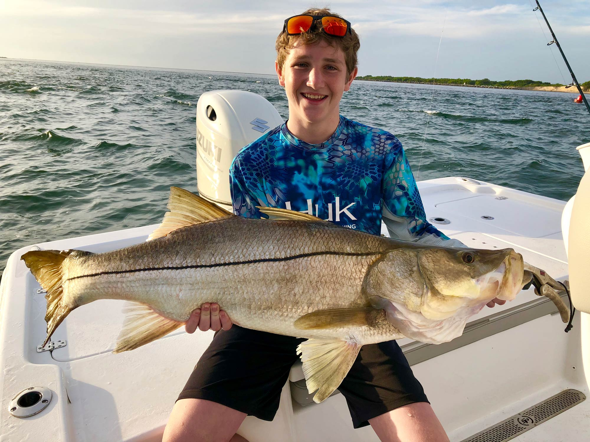 Smiling young angler holding a huge snook on a boat