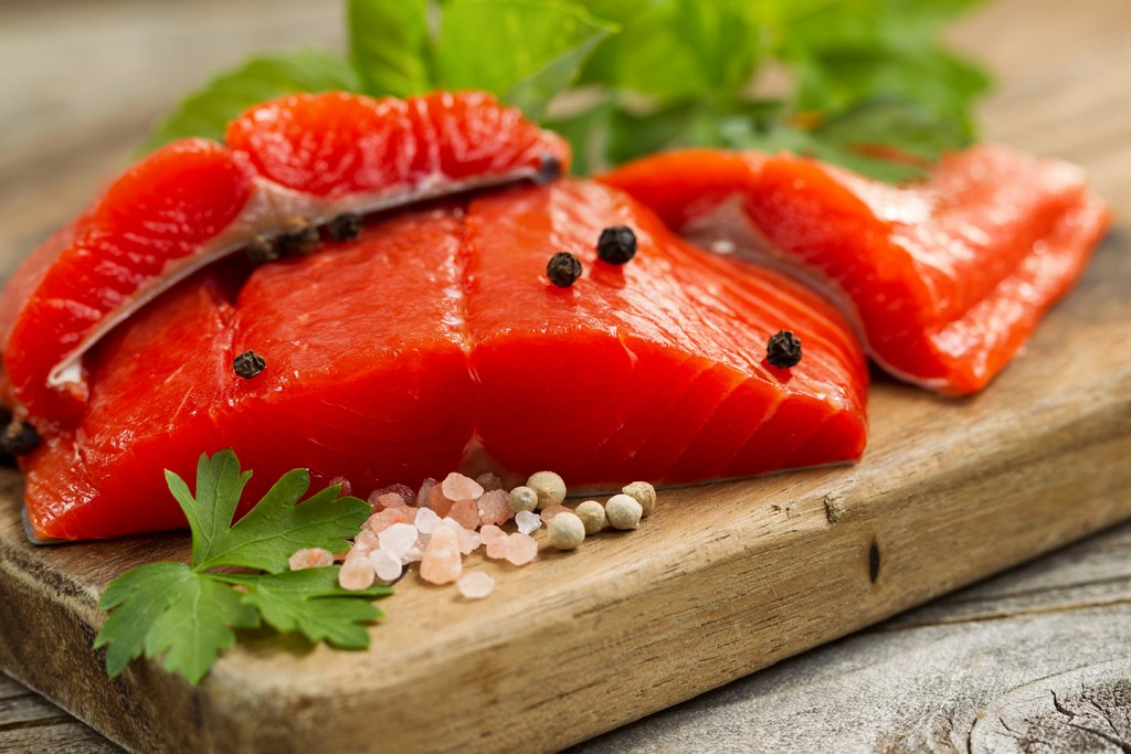 Three raw Sockeye Salmon fillets on a wooden board, with green herbs and salt and pepper laid around them as decoration. The red color of the fish is a clear sign that this is Salmon vs. Trout, which is usually more pink.