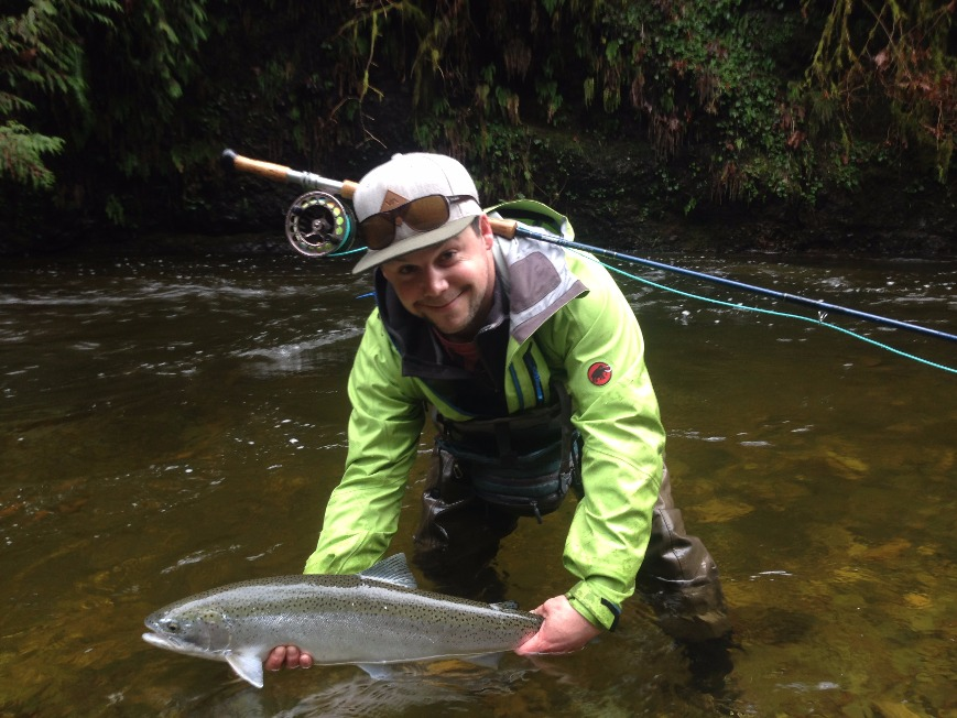 A fly angler standing in a river holds a Steelhead