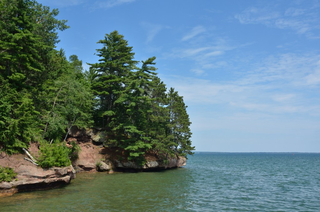 A view along Lake Superior, with green trees on the left