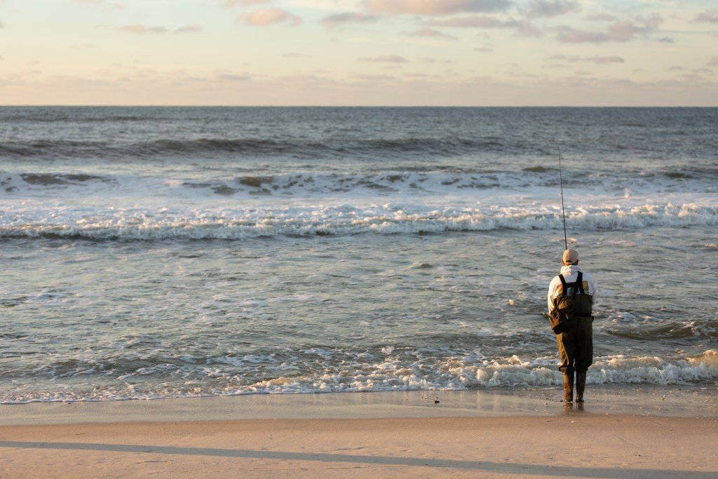 An angler in waders fishing on a beach on Long Island, NY