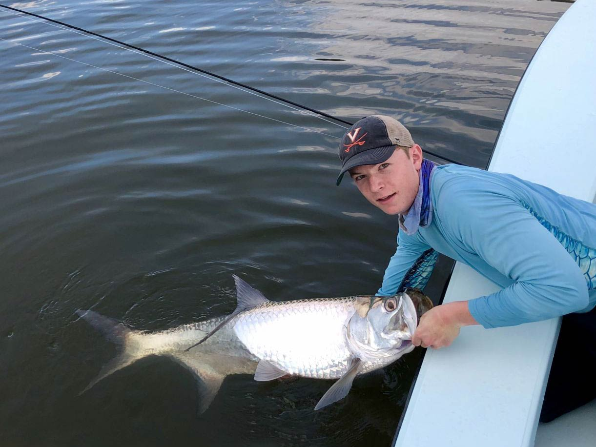Angler posing with a Tarpon he just caught while keeping the fish in the water