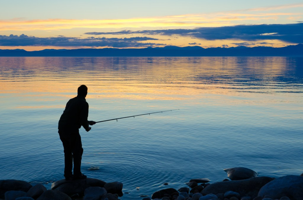 An angler fishing from shore at sunset