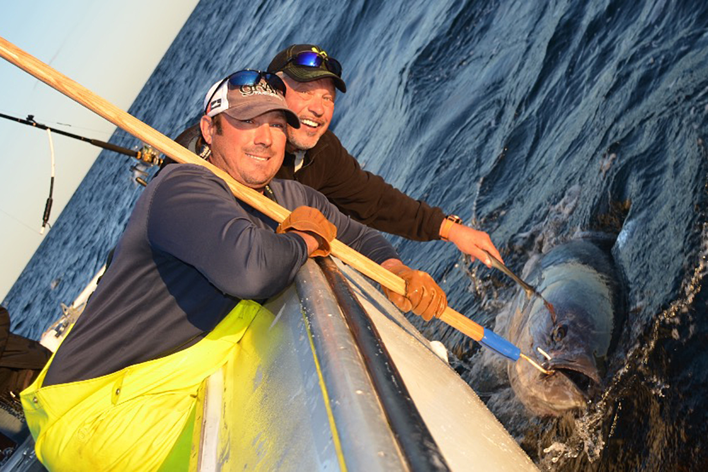 Two happy fishermen holding a Bluefin Tuna in the water next to them before they release it
