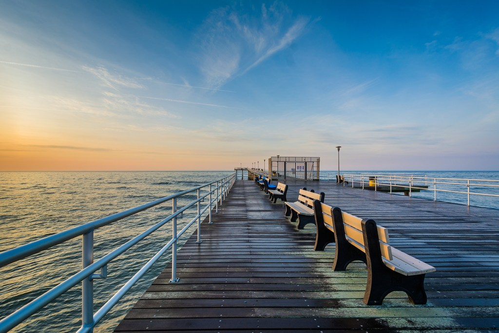 A view along Ventnor City Fishing Pier, one of the longest fishing piers in NJ, with the sun setting into the Atlantic Ocean in the distance.