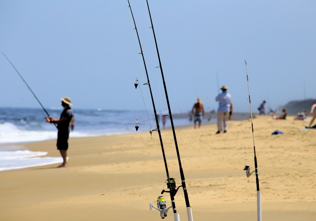 Two fishing rods set up on a beach, with a group of surf fishers in the distance.
