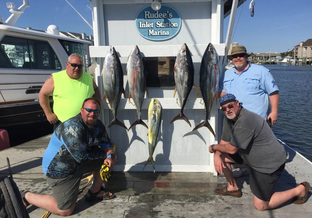 A group of anglers posing with four Tuna and a Mahi Mahi caught while fishing in Virginia Beach