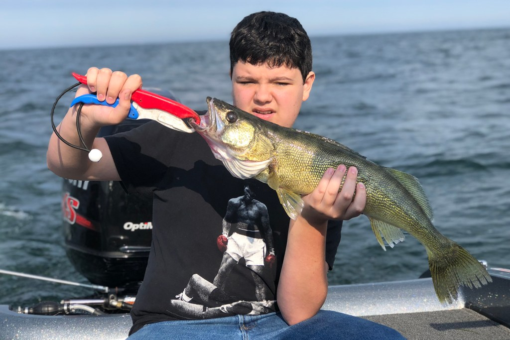A boy holding a Walleye on a fishing boat on Lake Erie.