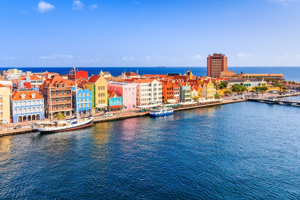 An aerial view of the waterfront in Willemstad, Curaçao, with colorful buildings, blue sea, and a sailboat moored at the dock.