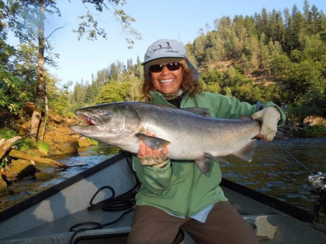 a smiling female angler holding a salmon on a fishing boat