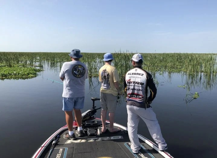 Three anglers fishing on a boat with a water and lake weeds in the background