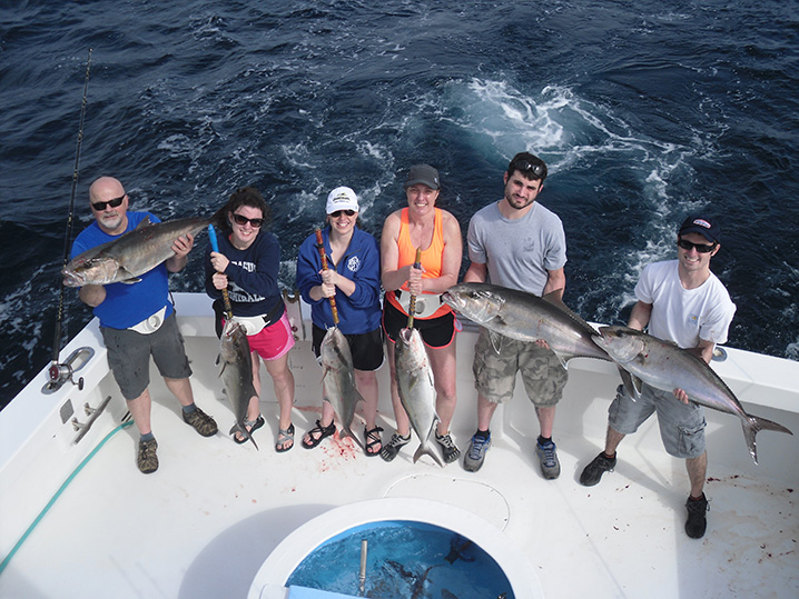 A group of anglers holding Amberjacks while fishing from a party boat in Destin