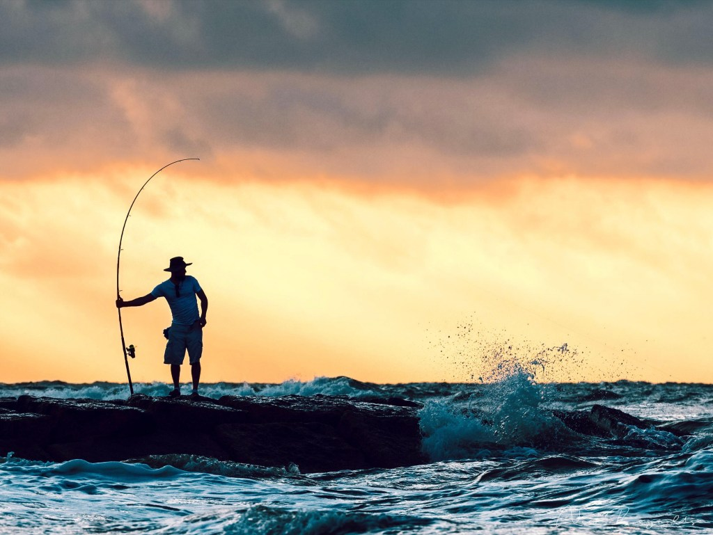 angler standing on a dock with a fishing rod in his hand