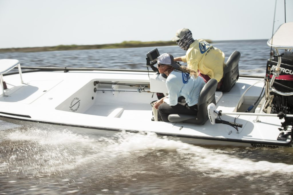 two men on a fast moving flats boat