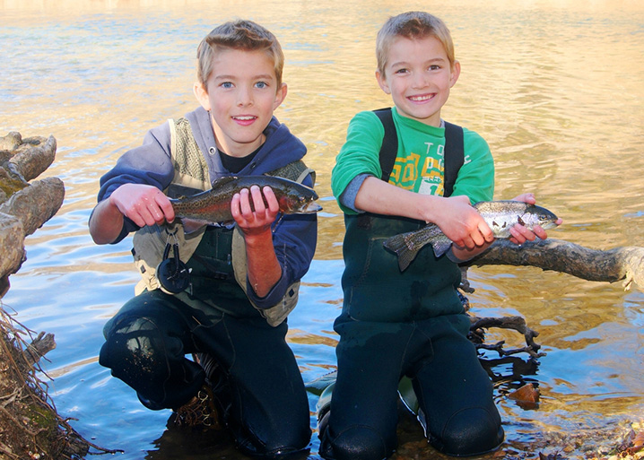 Two boys holding Trout which they caught on their fishing trip in Canyon Lake Park.