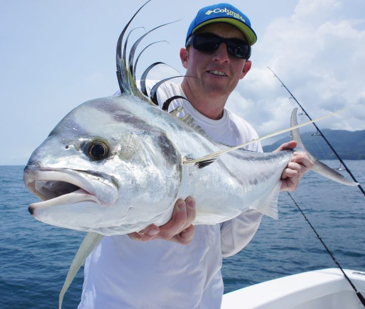 Man in a white shirt holding a large Roosterfish
