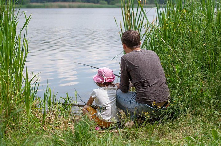 A dad and his daughter fishing together from a bank of a lake.