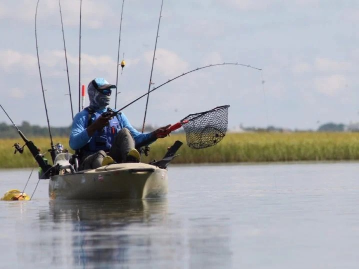 A man in a blue shirt and a hat holding a fishing rod and a net on a fishing kayak on the water with land in the background