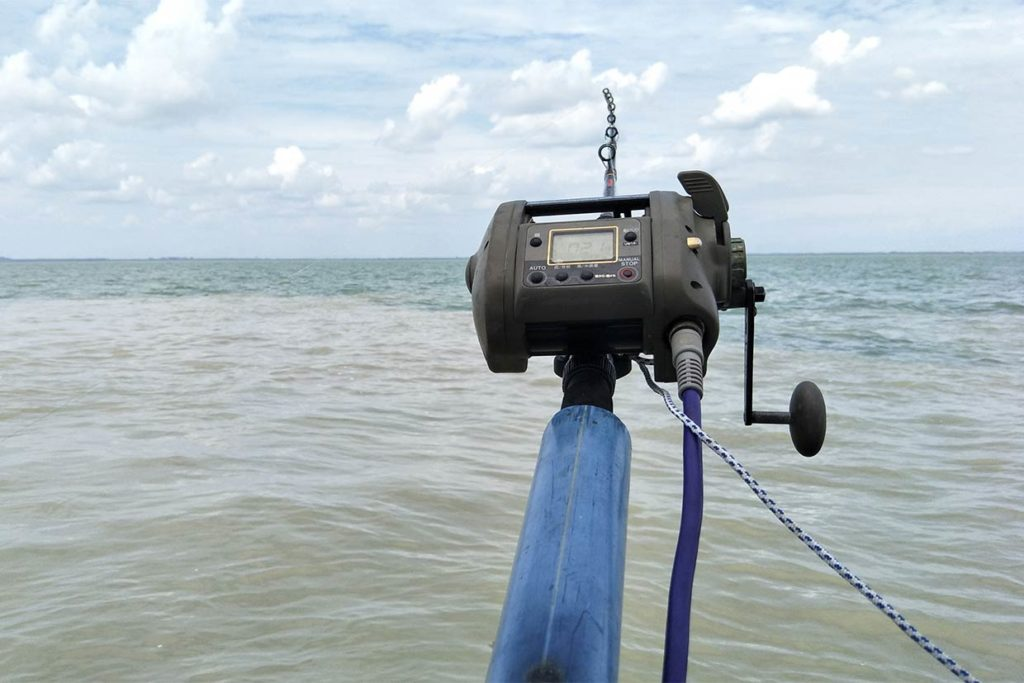 An electric reel drops a line deep into the ocean