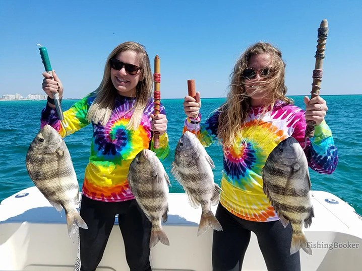 Two girls in colorful shirts holding Black Drum on a family fishing trip out of Destin, FL.