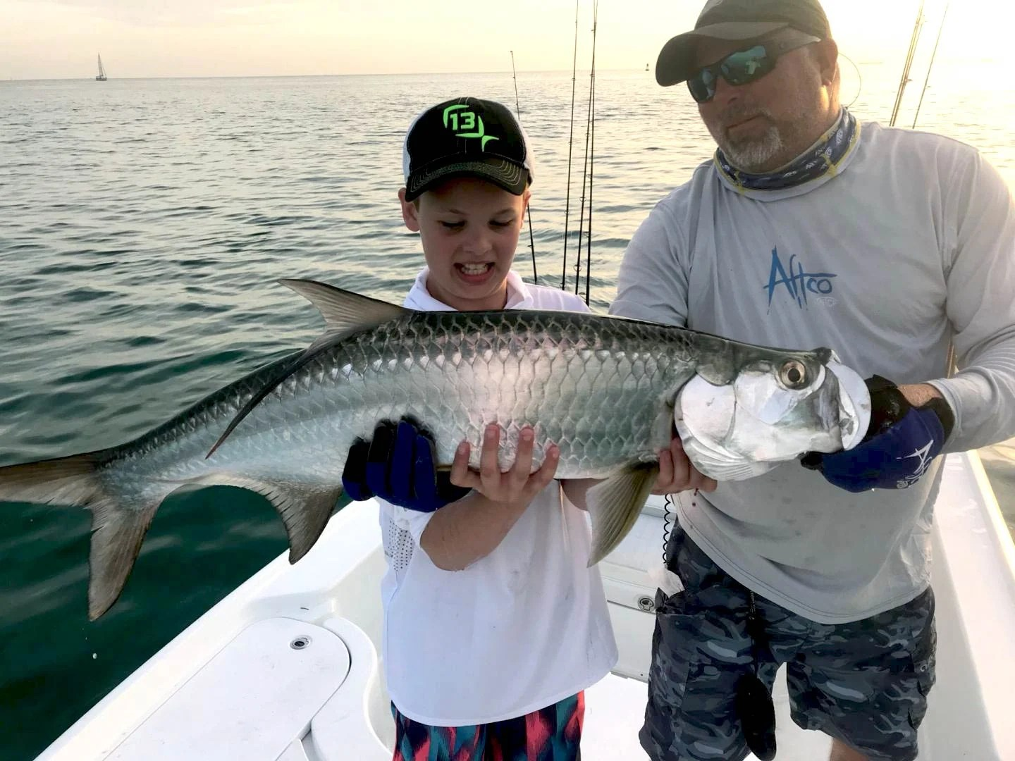 A man and a little boy holding a big Tarpon on a boat in Dry Tortugas
