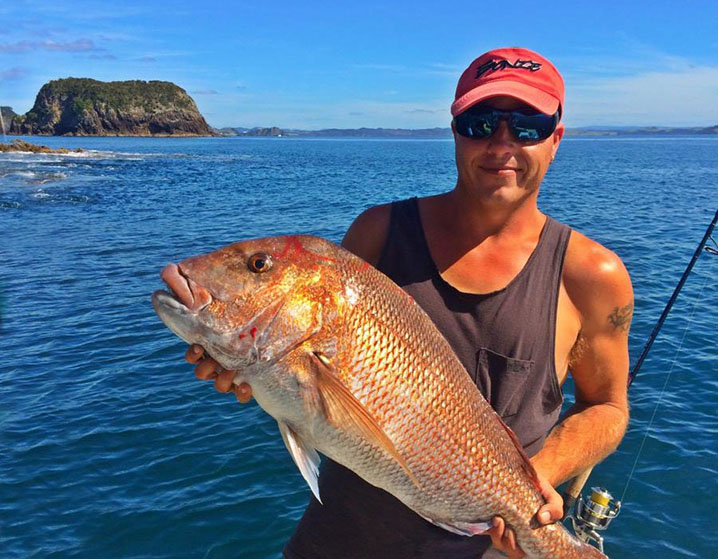 Photo of a man holding pink snapper with the explanation on taking great fishing photos