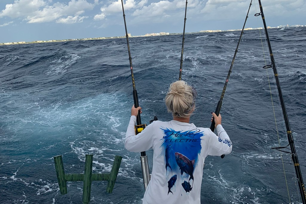 A woman holding on to two fishing rods on the back of a boat in rough weather.