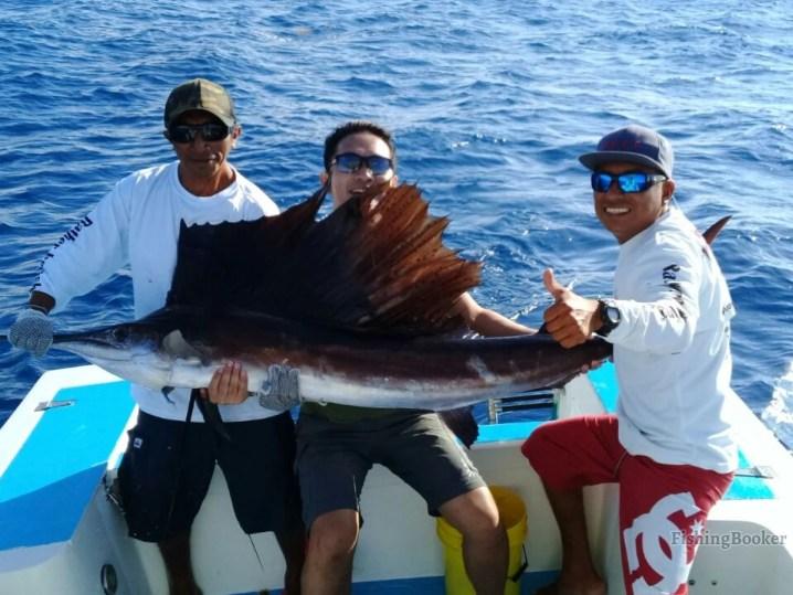 Fishing Riviera Maya: Angler holding a Sailfish he caught while fishing in Playa del Carmen