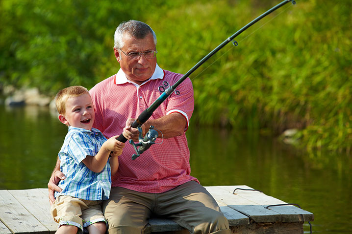 A grandfather teaching his grandson how to fish on a river bank