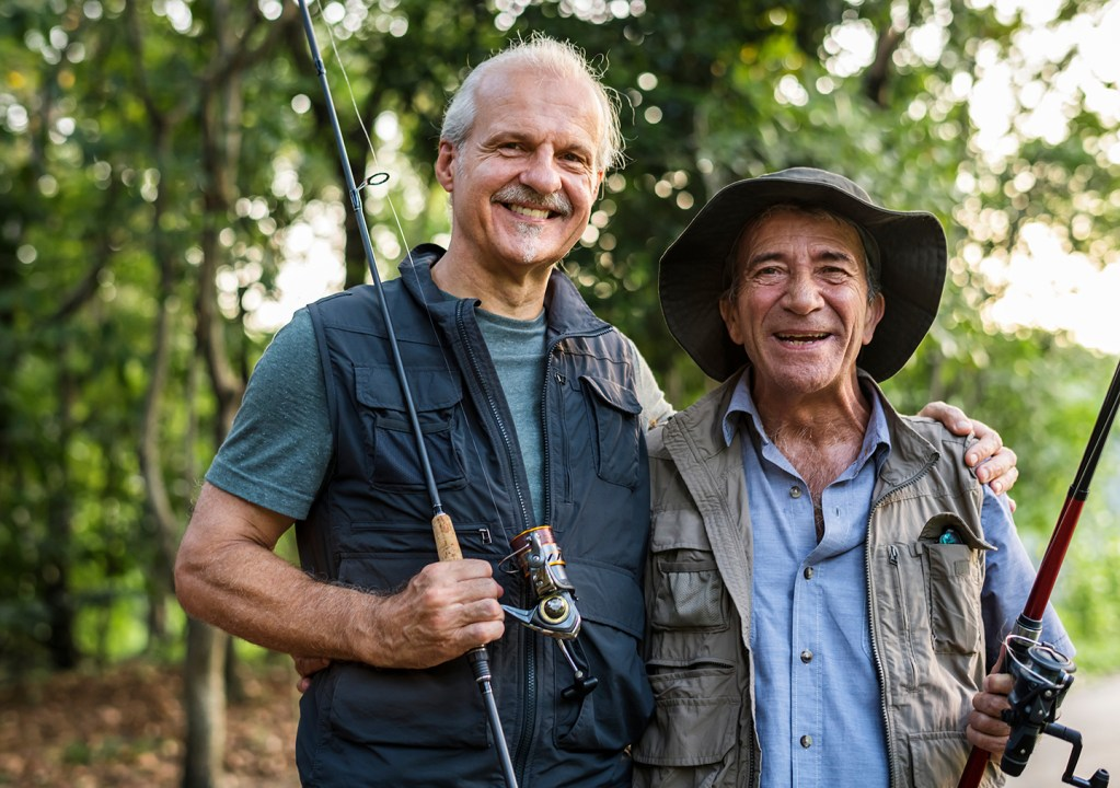 Two older anglers pose smiling for a photo.